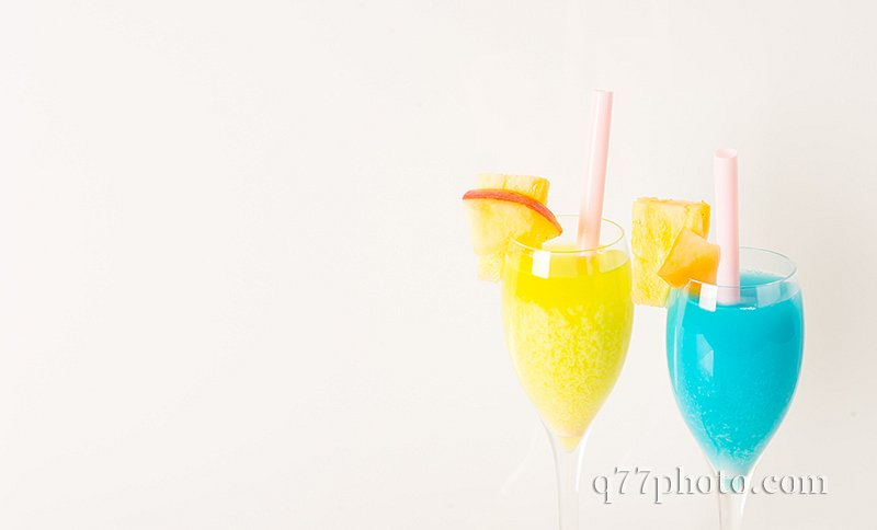 yellow and blue drinks decorated with fruit, drink straw, apple